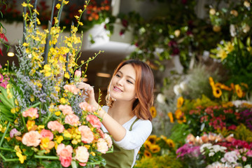 Pretty Vietnamese florist arranging flowers in shop