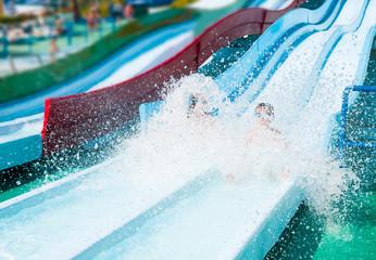Two children on water slide in aqua park