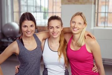 drei lachende frauen im fitness-club