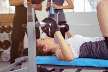 frau trainiert mit langhantel im fitnessstudio