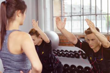 trainerin und sportler beim ems-training