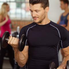 sportler trainiert bizeps im fitnessstudio