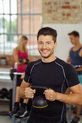 mann trainiert im fitnessstudio mit einem kettlebell