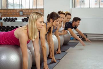 gruppe trainiert mit gymnastikbällen im fitness-studio