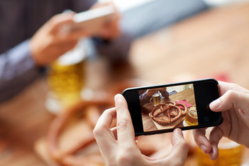 close up of hands picturing pretzel by smartphone