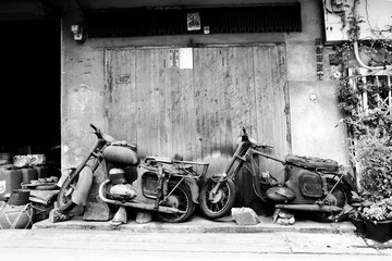 TWO CLASSIC MOTORCYCLE Two wrecked antique motorcycles parking in front of old shop house with wood doors.