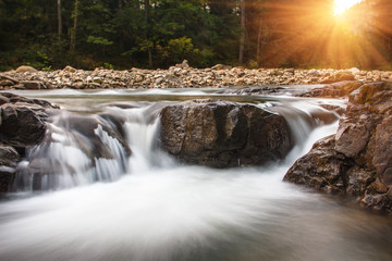 Landscape of mountain river in sunshine. View of the stony rapids. Fast jet of water at slow shutter speeds give a beautiful magic effect.