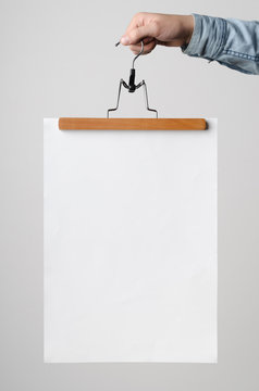 A3 Poster Mock-Up - Man holding a poster on a clothes hanger on a white background.