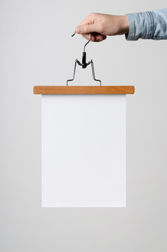 A4 Flyer / Poster Mock-Up - Man holding a poster on a clothes hanger on a white background.