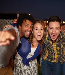 Multi-ethnic millenial friends taking a flash selfie with mobile phone on rooftop patio