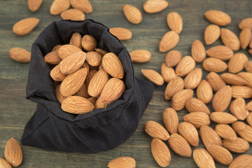 Almonds in the bag on the wooden background