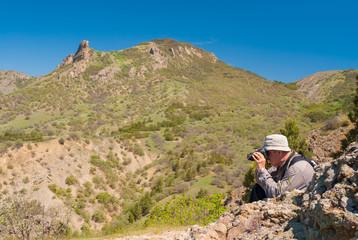 Photographer is taking photos on Kara-dag (extinct volcan) natural reserve, Eastern Crimea