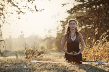 Young woman meditating while sitting on field