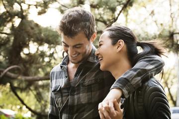 Cheerful romantic couple walking at park