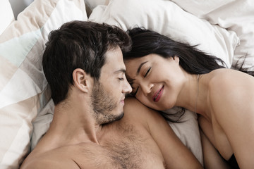 Overhead view of happy loving couple lying on bed
