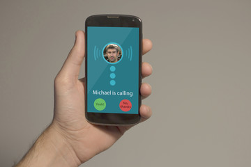 Hand holding smartphone with incoming call on the screen. All s