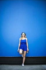 Full length of fashionable woman standing against blue wall