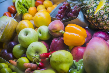 a lot of fruit: apples, pears, oranges, peppers, pineapple on store shelves closeup