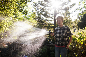 Female watering backyard with garden hose