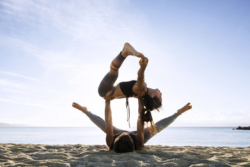 Man and woman practicing yoga on the beach against sky