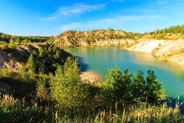 quarry or lake or pond with sandy beach, green water, trees