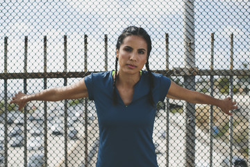Portrait of confident athlete standing against chainlink fence