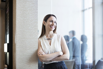 Happy businesswoman leaning on wall in office