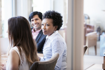 Mid adult woman looking at colleague during meeting in office