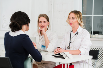 Two pretty young women nurses or doctors talking with female client in their office