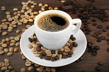 Cup of coffee with beans on wooden background