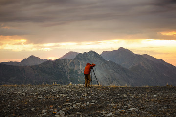 Rear view of man taking picture of mountains against cloudy sky