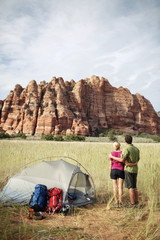 Rear view of couple standing by tent at grassy field against mountain