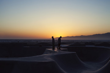 Silhouette skateboarders standing on ramp against clear sky during sunset