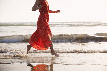 Low section of woman running on beach