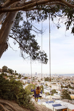 Woman swinging from branch with cityscape in background