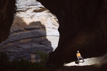 Sunlight falling on man standing in cave