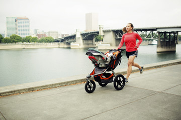 Woman jogging with baby stroller on footpath by river against bridge