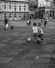 Ragazzini che giocano a calcio in una piazza di Napoli