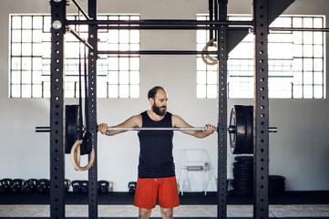 Man picking up barbell from rack in gym