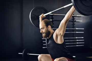 Male athlete lifting barbell at health club
