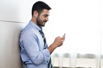 Side view of businessman using smart phone while leaning on wall in hotel room