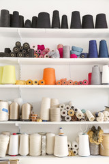 Colorful spools arranged on shelves at home