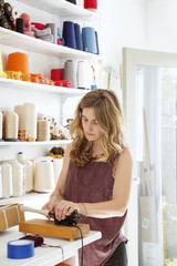 Woman spooling yarn while standing in studio