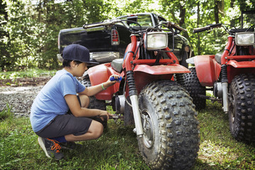 Boy repairing ATV on grass field