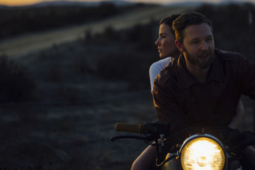 Young couple riding illuminated motorcycle at field