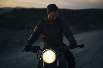 Man riding illuminated motorcycle on field