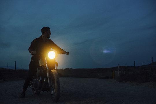 Man riding motorbike on street at night