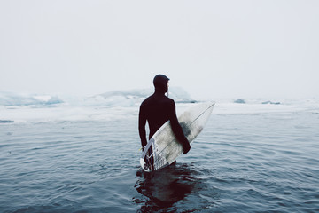 Man carrying surfboard while standing in icy sea