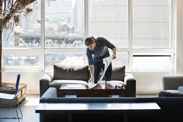 Businessman holding blueprint on table in office