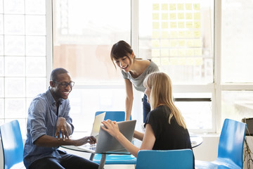 Businesswoman showing laptop to colleagues on table in creative office